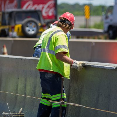 A worker smooths and levels the new barrier before the concrete sets.
