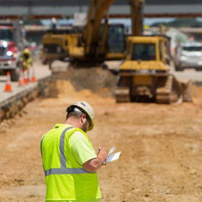 An inspector takes notes on the progress of the future I-95 Express Toll Lanes.